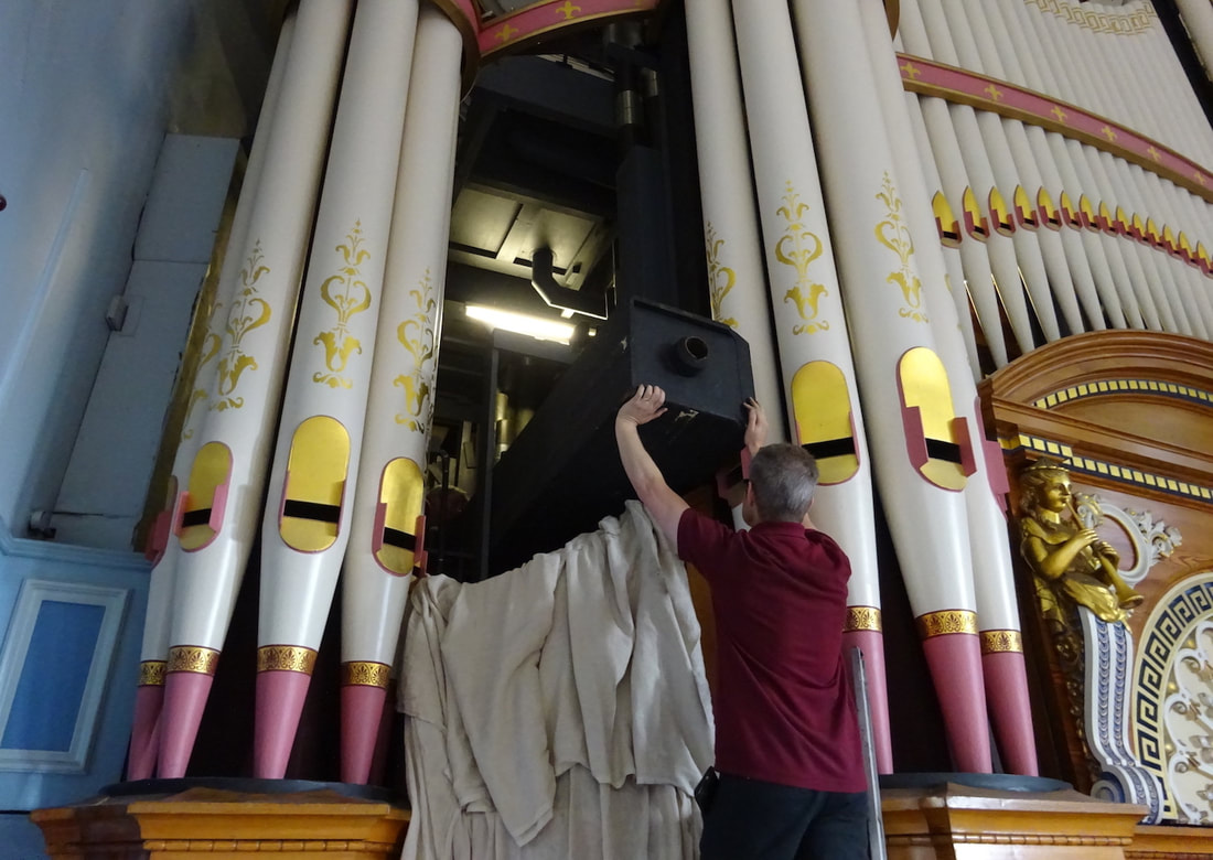 A team of organ builders get ready to return the pipe to its restored chest