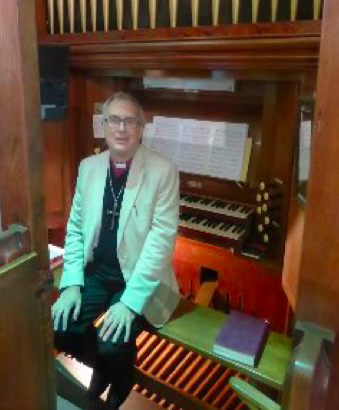 Bishop Paul sits at the newly restored organ in Christ Church, Great Ayton.