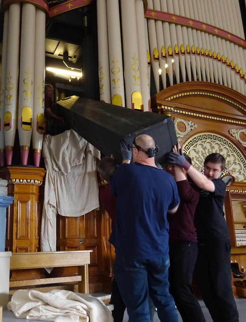 The large organ pipe is received in the organ chamber by invisible hands